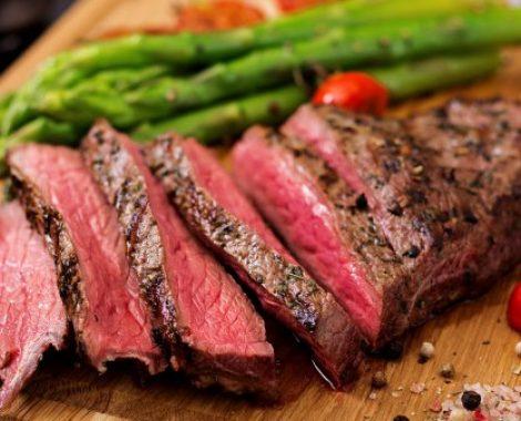saftiges-steak-seltenes-rindfleisch-mit-gewuerzen-auf-einem-holzbrett-und-garnierung-von-spargel_2829-1513